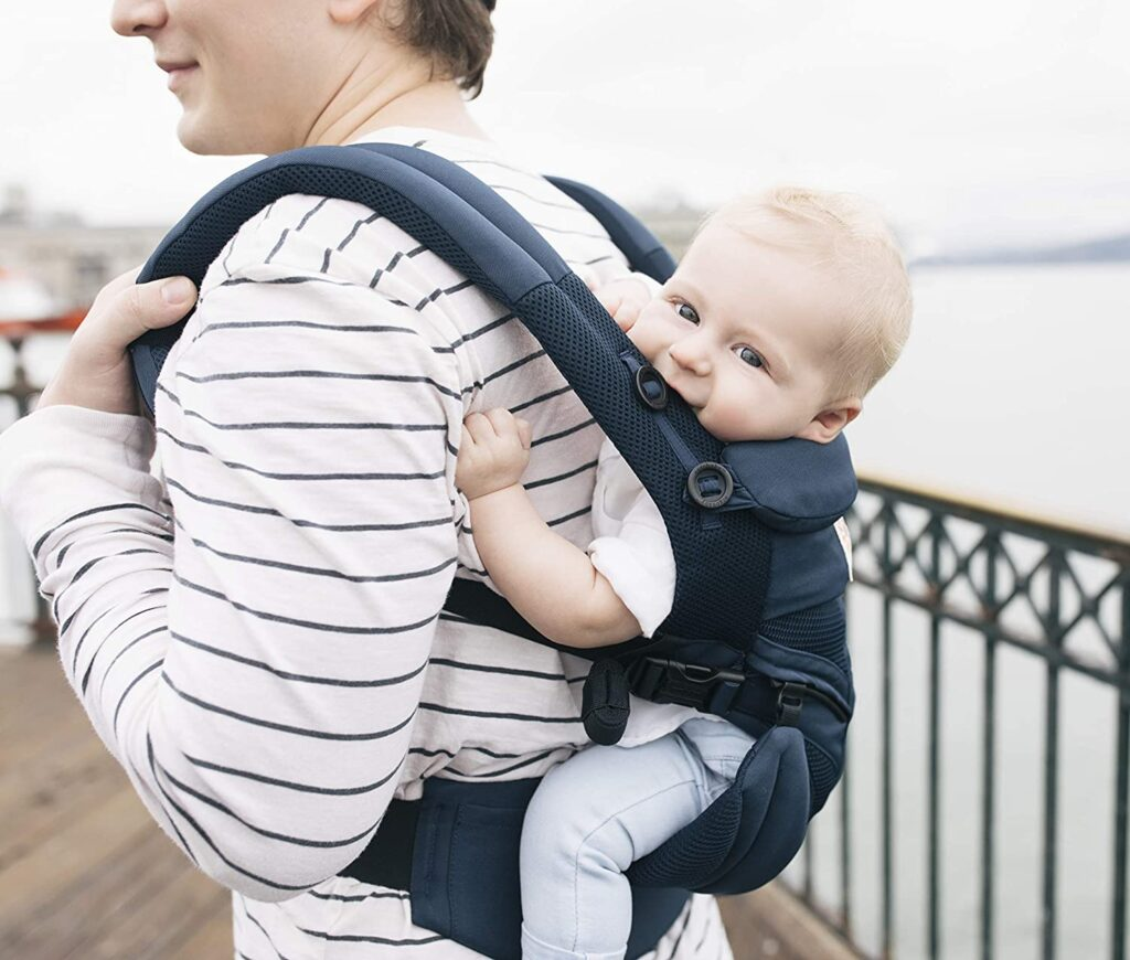 Model carrying baby on her back in the Ergobaby Omni 360 cool mesh in Midnight Blue