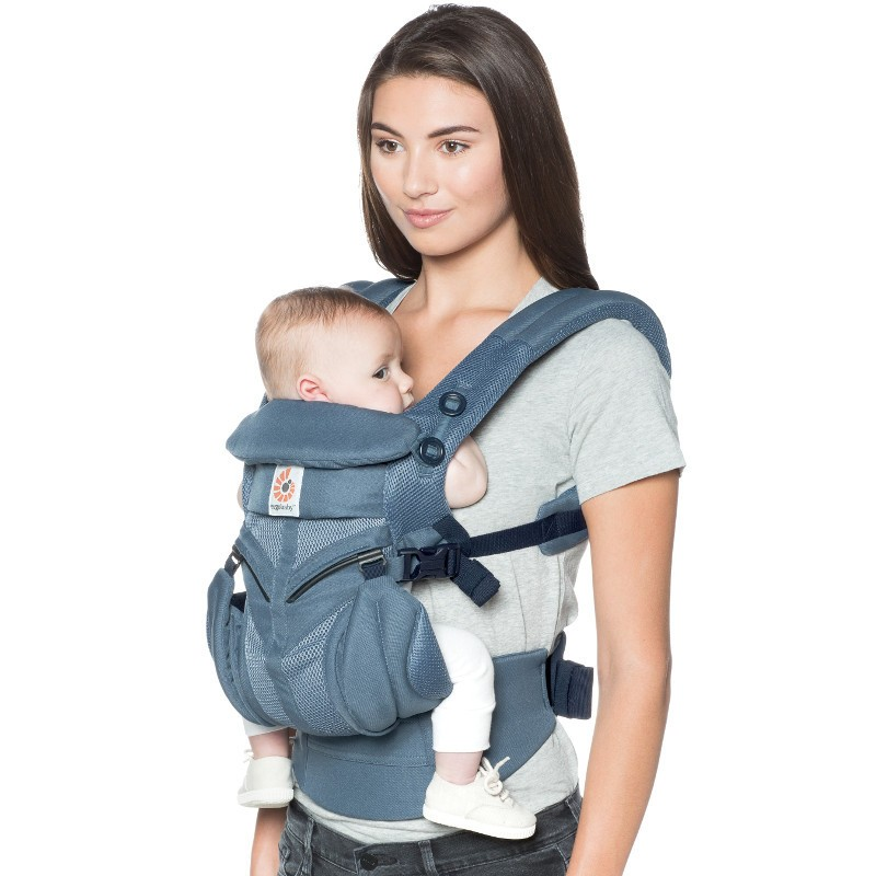 Female model carrying a baby in Ergobaby Omni 360 cool mesh in oxford blue
