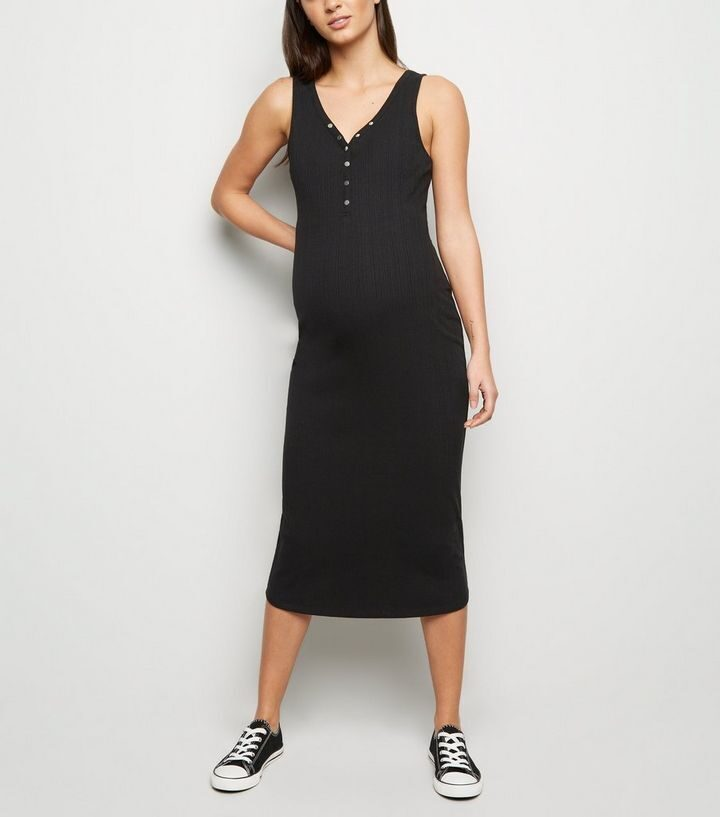 Model wearing New Look ribbed bodycon maternity dress in black- front view