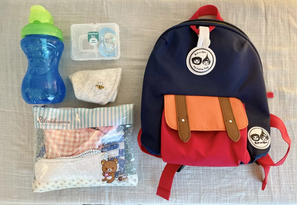 Showing the contents of Zip and Zoe mini backpack in navy colourblock - Nuby water bottle, pacifier, bib, clothes