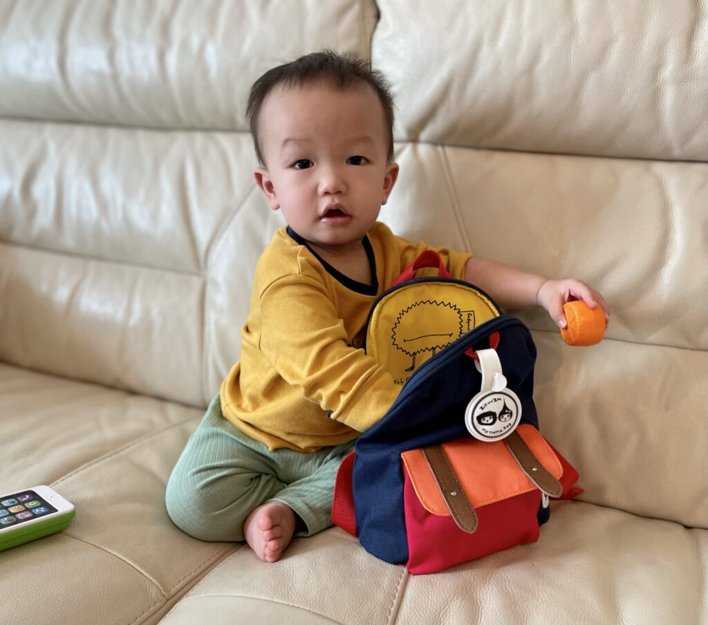 1 year old toddler taking things out of Zip & Zoe mini backpack in navy colourblock