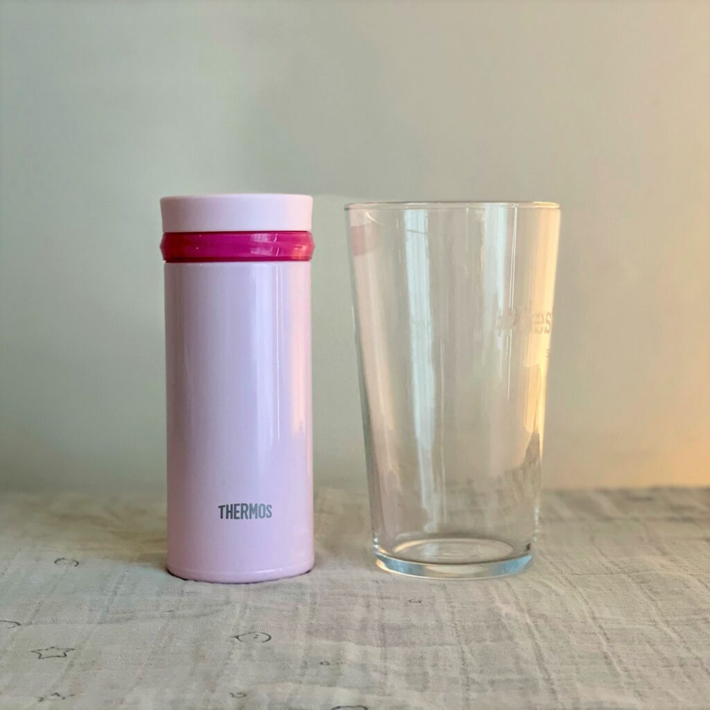 Pink 250ml Thermos and a UK pint glass to compare the size
