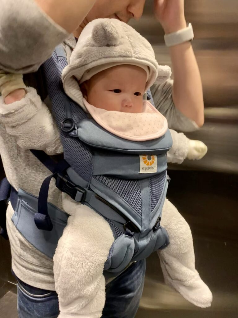 Father carrying baby in Ergobaby Omni 360 cool mesh in oxford blue - side view