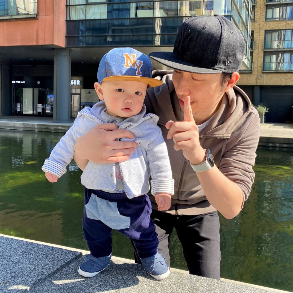 9 month old baby wearing Matalan navy denim velcro pram shoes, with father by the river