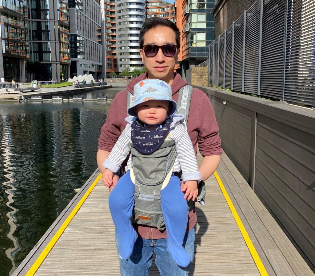 Father carrying 10 month old baby in the Amazon Sunveno hip seat carrier by the canal
