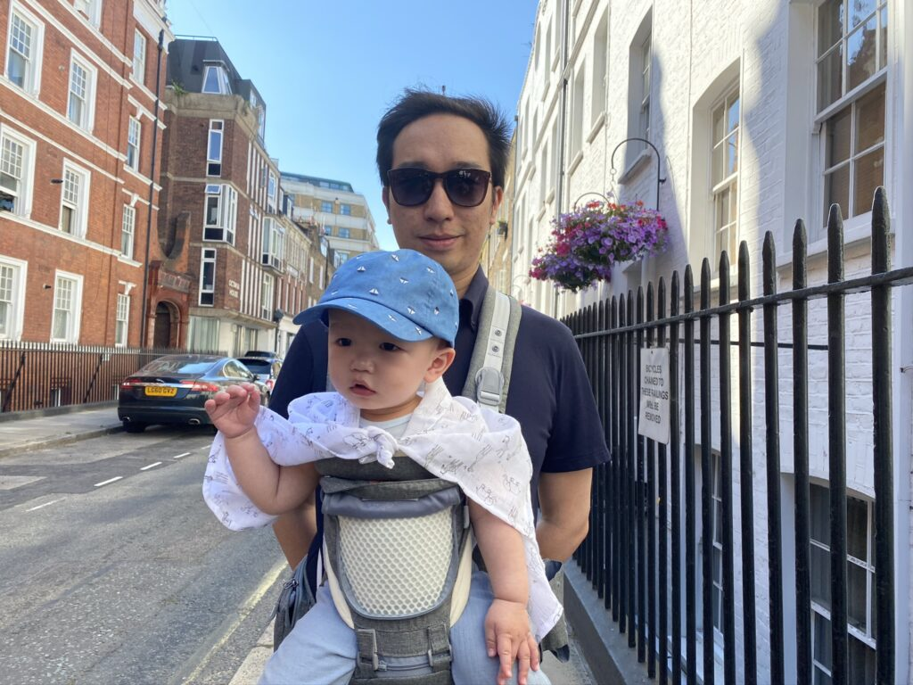 Father carrying 10 month old baby in the Amazon Sunveno hip seat carrier with the front panel unzipped