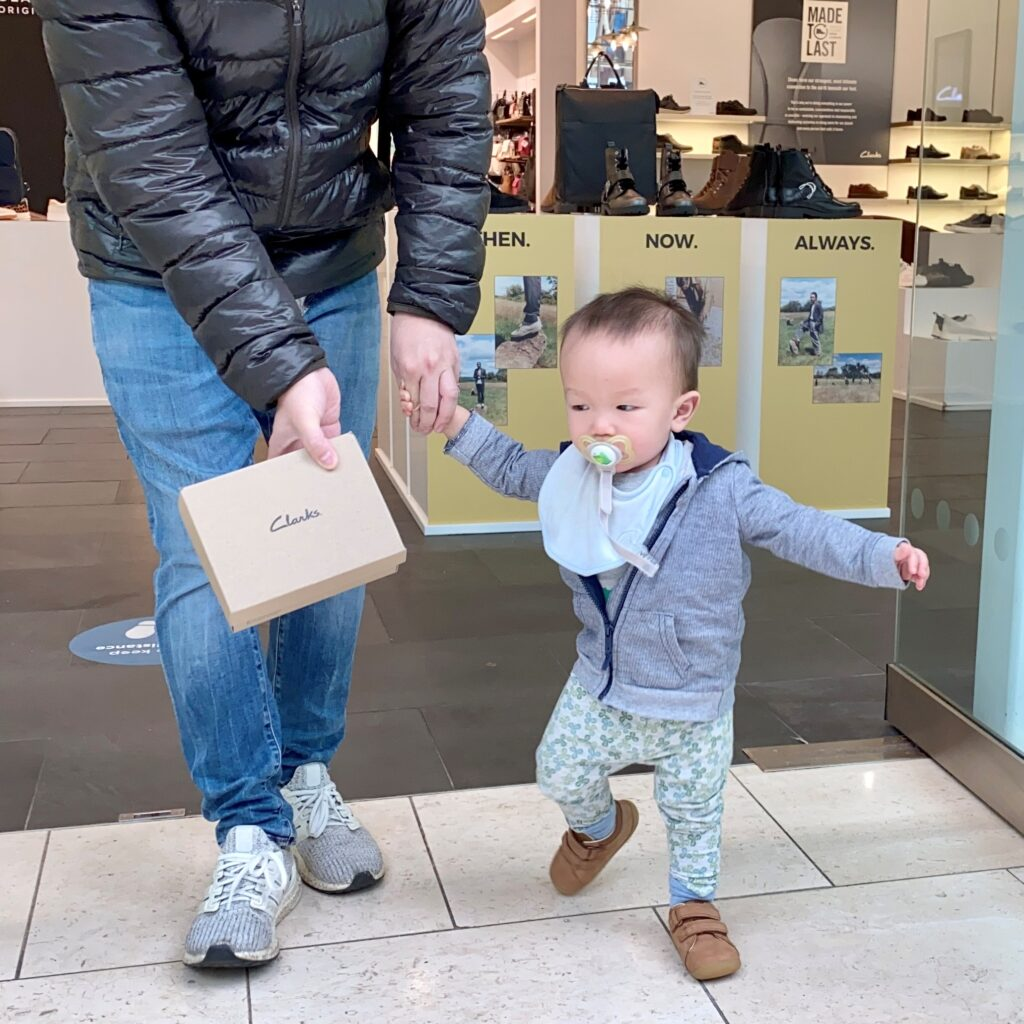 1 year old boy coming out of clarks with new shoes