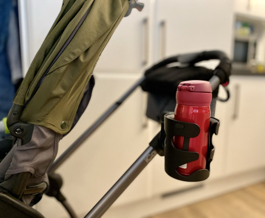 Author's iCandy universal cup holder attached to pushchair frame holding pink thermos