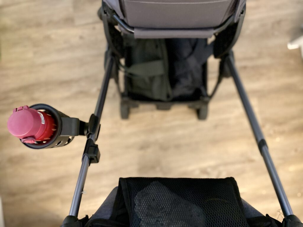 Author's iCandy universal cup holder attached to outside of pushchair frame holding pink thermos