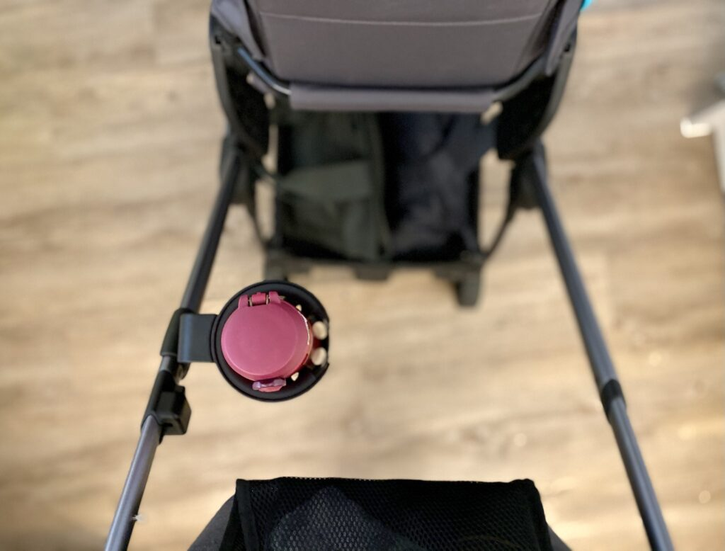 Author's iCandy universal cup holder attached to inside of pushchair frame holding pink thermos