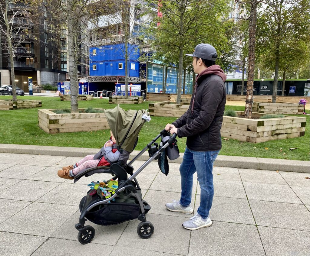 Father pushing baby in iCandy Raspberry Pushchair in Kings Road Khaki with elevators