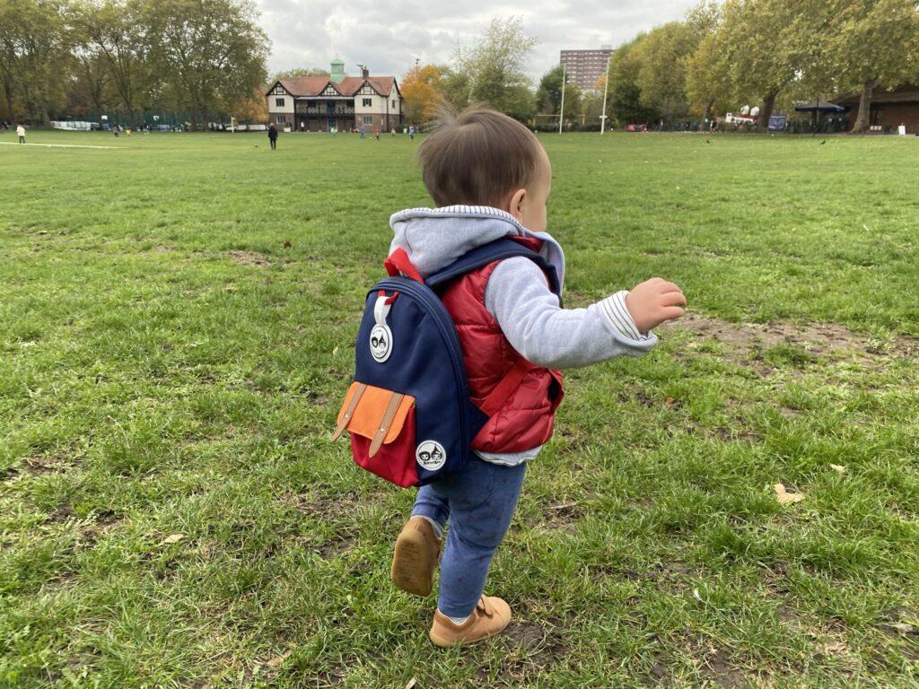 1 year old toddler wearing Zip & Zoe mini backpack in navy colourblock