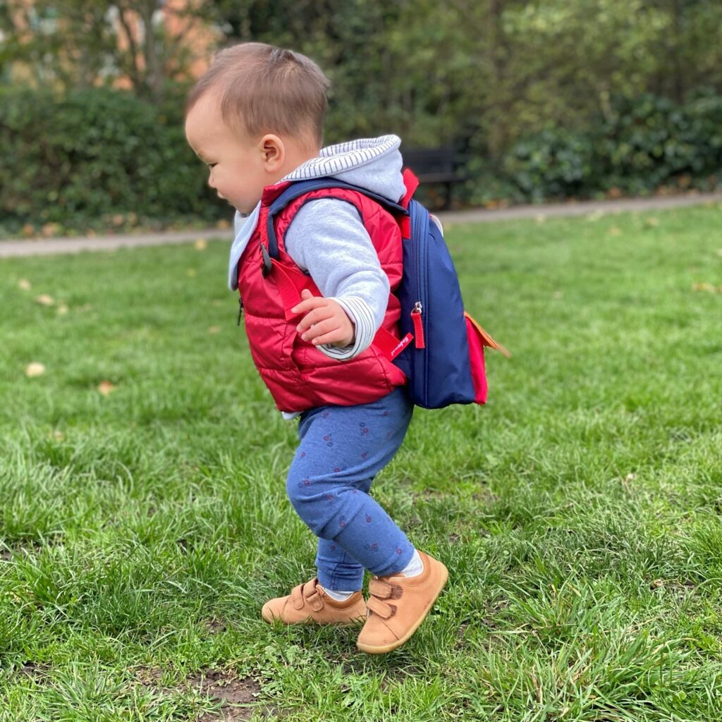 1 year old boy on the grass wearing Clarks Roamer Craft shoes