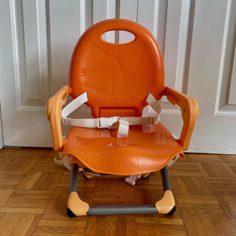 Author's Chicco Pocket Snack Booster Seat in orange with legs folded out front view