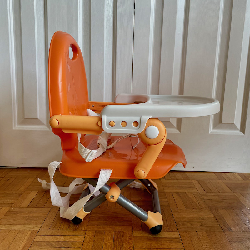 Author's Chicco Pocket Snack Booster Seat in orange with tray and legs folded out side view