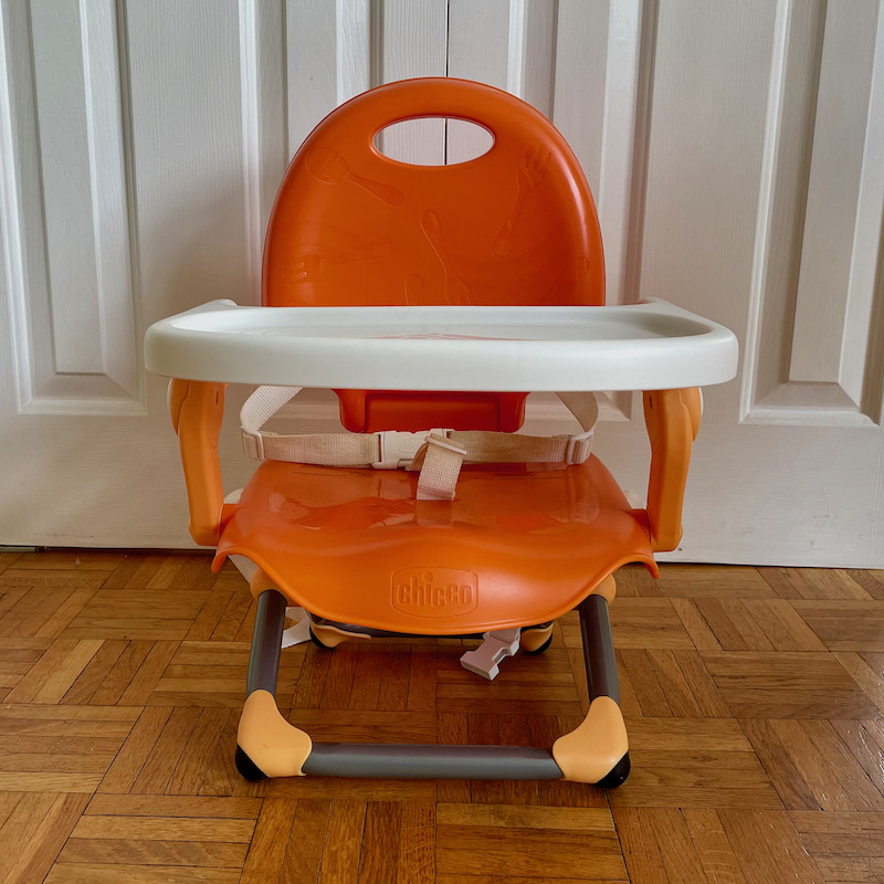 Author's Chicco Pocket Snack Booster Seat in orange with tray and legs folded out front view