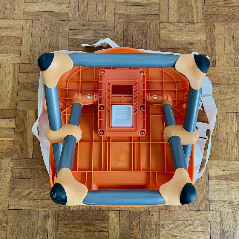 Author's Chicco Pocket Snack Booster Seat in orange underneath showing legs