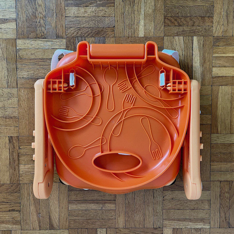 Author's Chicco Pocket Snack Booster Seat in orange folded showing underneath