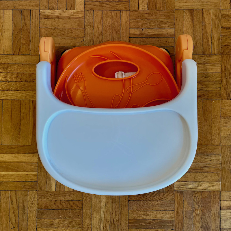 Author's Chicco Pocket Snack Booster Seat in orange folded flat view from above