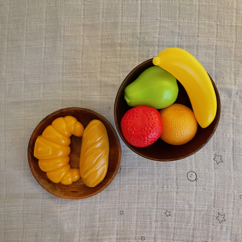 Plastic fruit and bread in wooden bowls