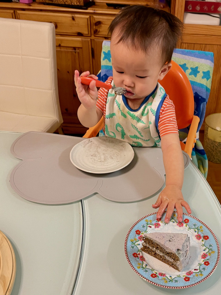 Jin reaching for more smash cake with blueberry whipped cream