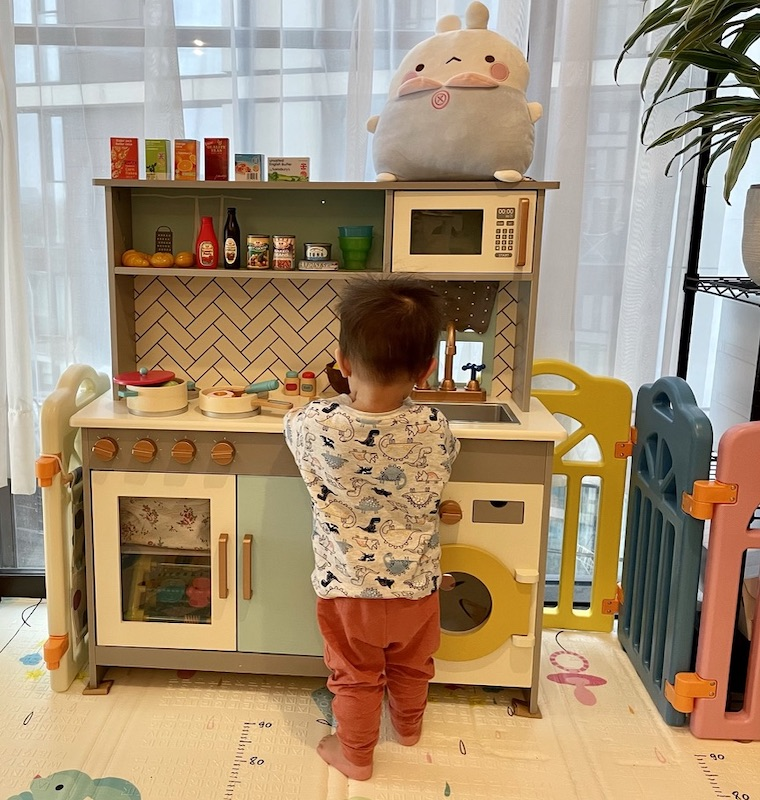Boy playing with toy kitchen
