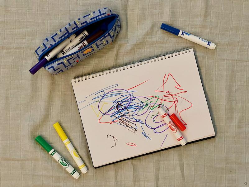 Crayola Pens scattered next to sketchbook